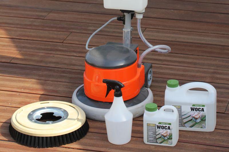 Hier sehen Sie die geeigneten Putz-Utensilien. Wichtig ist der Woca Exterior Cleaner, ein speziell konzipierter Reiniger für Holz im Außenbereich. Um die Arbeit zu erleichtern empfiehlt sich die Benutzung einer Tellerschleifmaschine. Notwendig ist hierfür ein Nylonbürsten-Aufsatz. Alternativ kann der Terrassenboden händisch gesäubert werden.